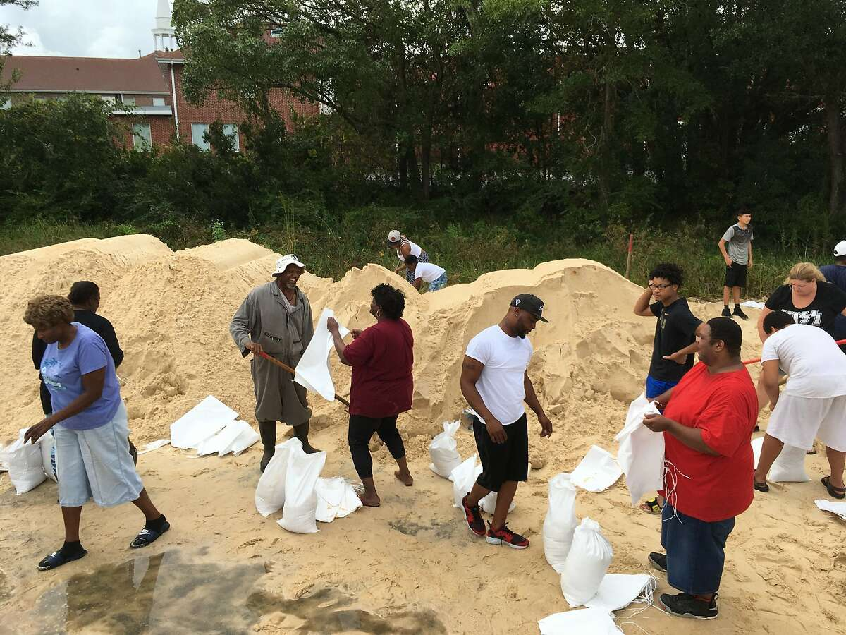 People fill sandbags to prepare for Hurricane Nate in Moss Point, Miss., on Saturday, Oct. 7, 2017. Storm surge threatens many low-lying neighborhoods in city, which was heavily flooded during 2005's Hurricane Katrina. (AP Photo/Jeff Amy)
