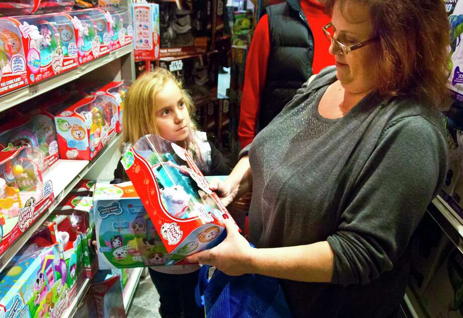 "FILE - In this Friday, Nov. 27, 2015, file photo, Cinnamon Boffa, right, from Bensalem, Pa., checks out a ""Chubby Puppies"" toy for her daughter Serenity, left, at a Toys R Us, in New York. With some holiday toys already in stores, shoppers may want to start planning their strategy. (AP Photo/Bebeto Matthews, File) ORG XMIT: NYBZ333 Photo: Bebeto Matthews / Copyright 2016 The Associated Press. All rights reserved."