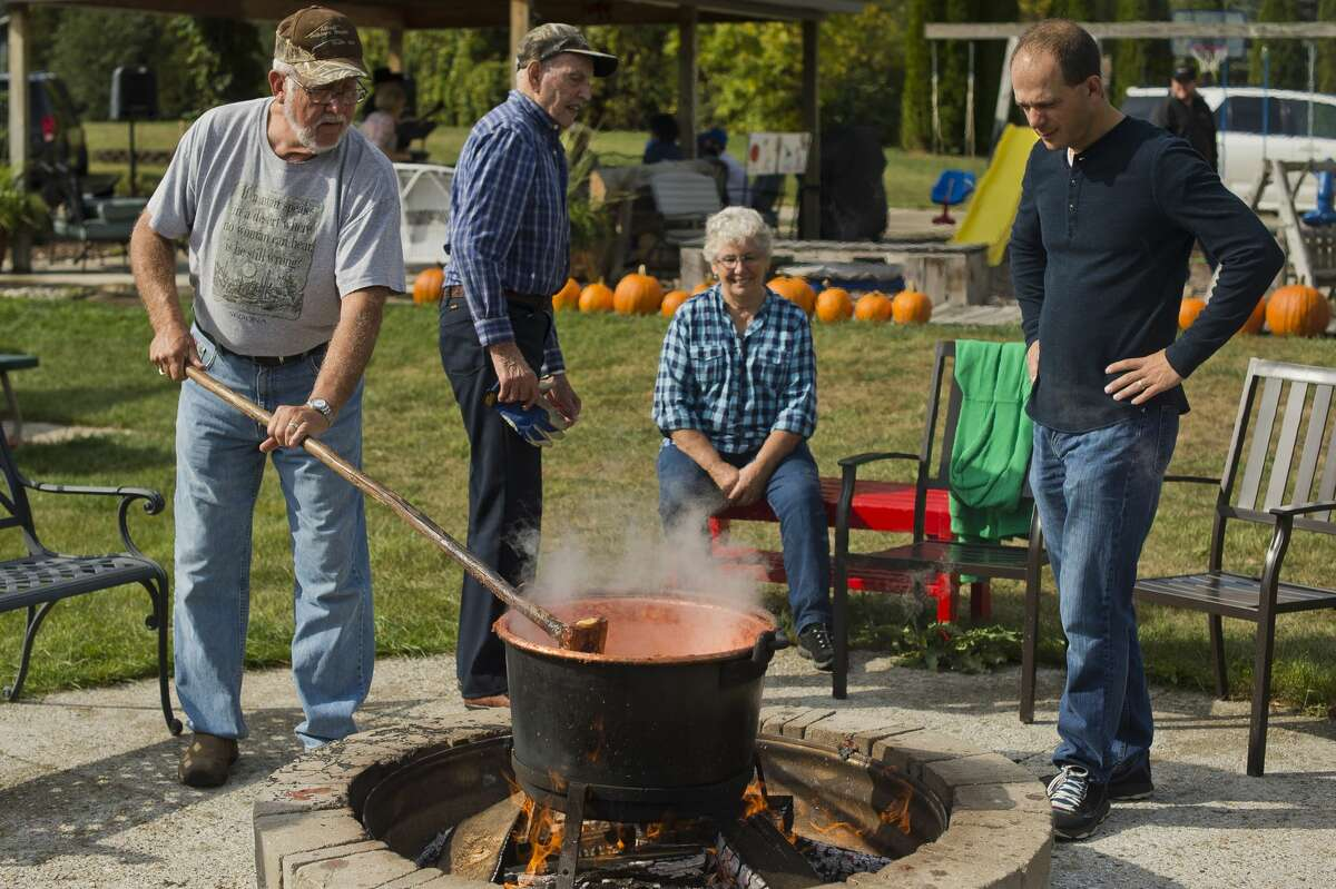 People take turns stirring a pot of apple butter during the annual Apple Butter Day at Apple Blossom Orchard on Saturday, Oct. 7, 2017 in Midland. (Katy Kildee/kkildee@mdn.net)