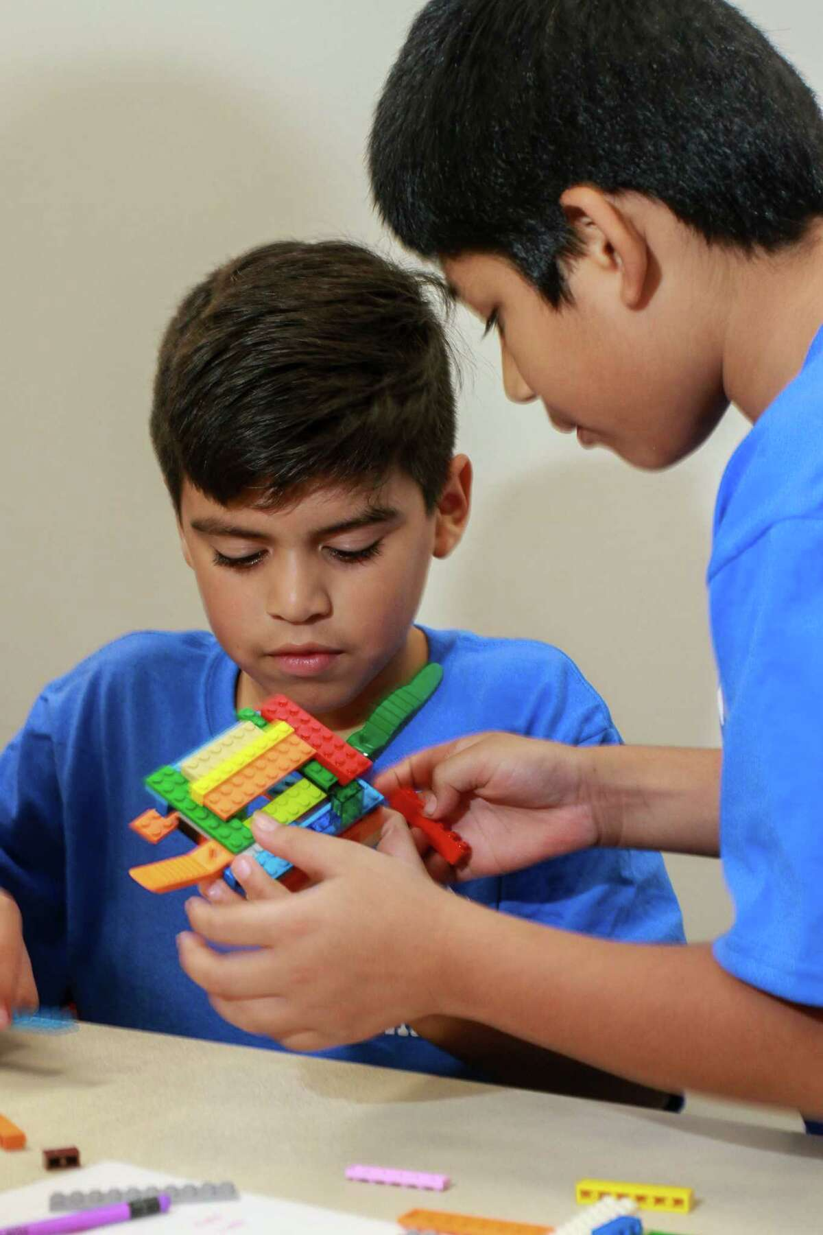 Joshua Gutierrez, 11, left, and John Acosta, 9, building a Lego boat as they learn about careers in STEM fields, part of the Comcast TechPak program. (For the Chronicle/Gary Fountain, October 7, 2017)
