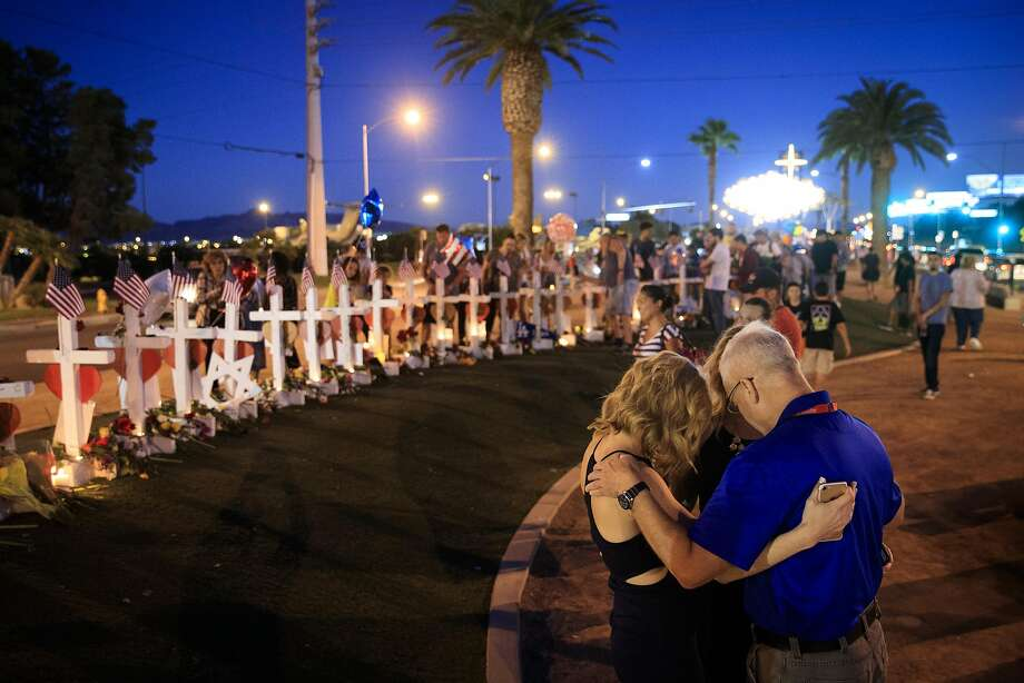 Observers embrace and pray Saturday night at a memorial with 58 white crosses, one for each victim, on the Las Vegas Strip. Investigators are still trying to determine a motive for the attack. Photo: Drew Angerer