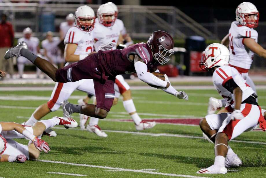 Magnolia's Michael Woods goes airborne over the defense into Tomball's Dezmun Martinez in the first half of their game at Bulldog Stadium in Magnolia, TX, Oct. 5, 2017. (Michael Wyke / For the  Chronicle) Photo: Michael Wyke, Freelance / © 2017 Houston Chronicle