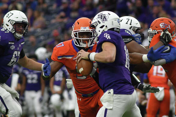 Sam Houston State junior defensive tackle Chris Stewart (97) pressures Stephen F. Austin sophomore quarterback Jake Blumrick (10) after beating Blumrick's teammate Jaxon Salinas (67) during the 2nd quarter of their Battle of the Piney Woods clash at NRG Stadium in Houston on Saturday, Oct. 7, 2017. (Photo by Jerry Baker/Freelance)