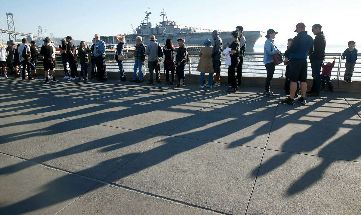 Visitors wait in line for a security checkpoint before taking a public tour of the US Navy amphibious assault ship USS Essex during Fleet Week in San Francisco, Calif. on Saturday Oct. 7, 2017.
