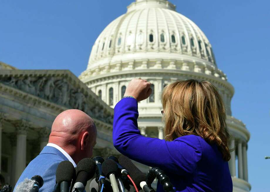 "Former Rep. Gabrielle Giffords, D-Ariz., right, shakes her fist at the United States Capitol as she and her husband Mark Kelly, left, speak on Capitol Hill in Washington, Monday, Oct. 2, 2017, about the mass shooting in Las Vegas. Giffords raised her fist at the Capitol and said ""the nation is counting on you"" after the deadly mass shooting in Las Vegas. (AP Photo/Susan Walsh) Photo: Susan Walsh, STF / Copyright 2017 The Associated Press. All rights reserved."