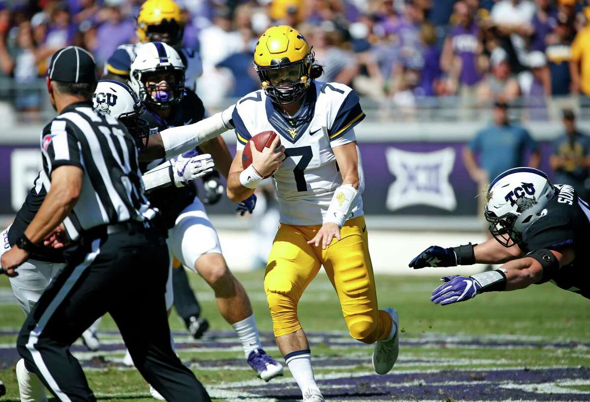 West Virginia quarterback Will Grier (7) scrambles as TCU linebacker Ty Summers, right, tries to stop him during the first half of an NCAA college football game Saturday, Oct. 7, 2017, in Fort Worth, Texas.