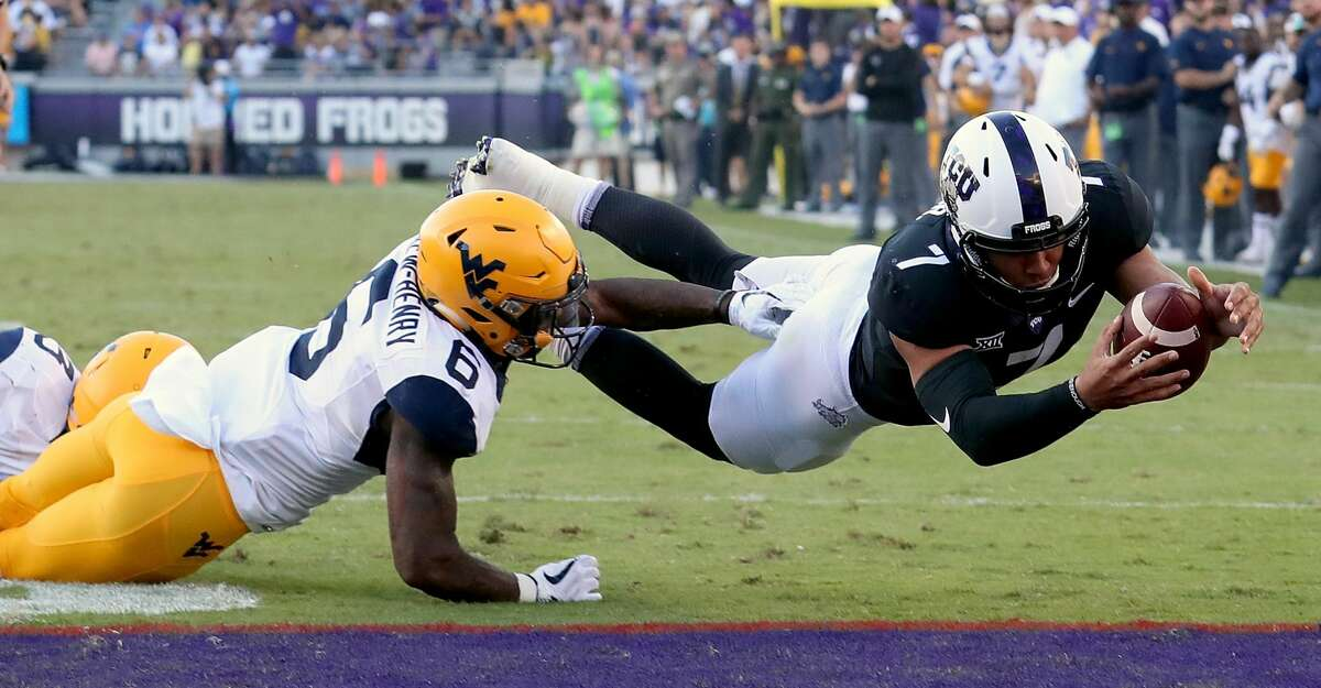 FORT WORTH, TX - OCTOBER 07: Kenny Hill #7 of the TCU Horned Frogs dives into the end zone to score the game winning touchdown against Dravon Askew-Henry #6 of the West Virginia Mountaineers in the fourth quarter at Amon G. Carter Stadium on October 7, 2017 in Fort Worth, Texas. The TCU Horned Frogs beat the West Virginia Mountaineers 31-24. (Photo by Tom Pennington/Getty Images)