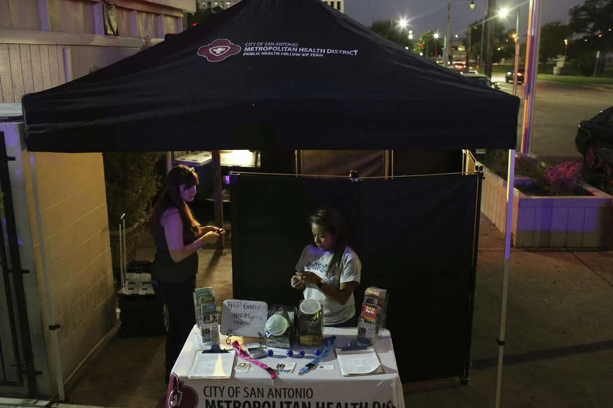 A volunteer with the San Antonio Metropolitan Health Department, Gabriela Guerra, left, and an intern, Mercedes Medina, set up for free testing for sexually transmitted diseases at Pegasus Night Club on Sept. 11. New diagnoses of HIV in Bexar County have increased by 50 percent over the last decade. Testing is a key step in reversing that trend.