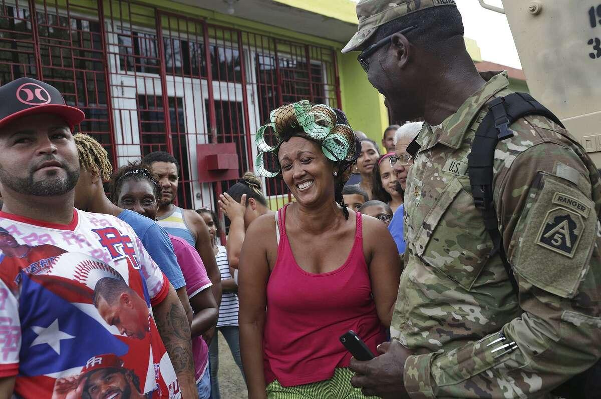 Marelin Oleo Ortiz laughs with Major Isaac Henderson, aide to Lt. Gen. Jeffrey Buchanan, after Henderson took a selfie with her.