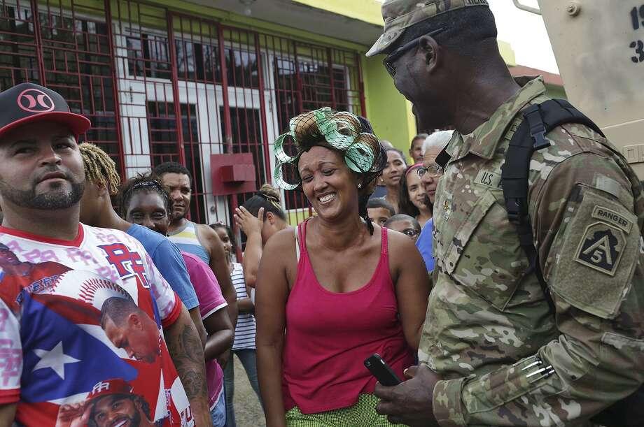Marelin Oleo Ortiz laughs with Major Isaac Henderson, aide to Lt. Gen. Jeffrey Buchanan, after Henderson took a selfie with her. Photo: Lisa Krantz / SAN ANTONIO EXPRESS-NEWS / SAN ANTONIO EXPRESS-NEWS
