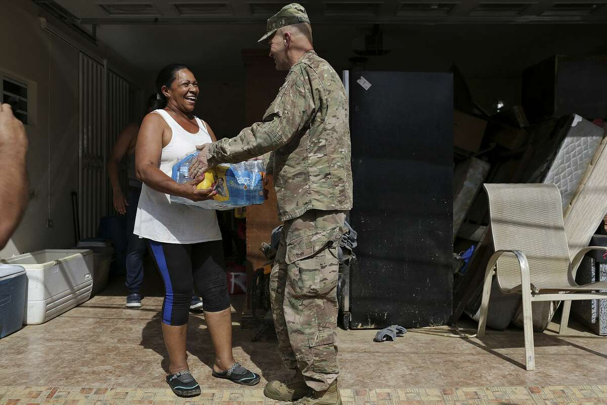 Lt. Gen. Jeffrey Buchanan helps deliver water to residents, including Ramona Mora, in the San Isidro neighborhood. Residents there don't have electricity or funning water.