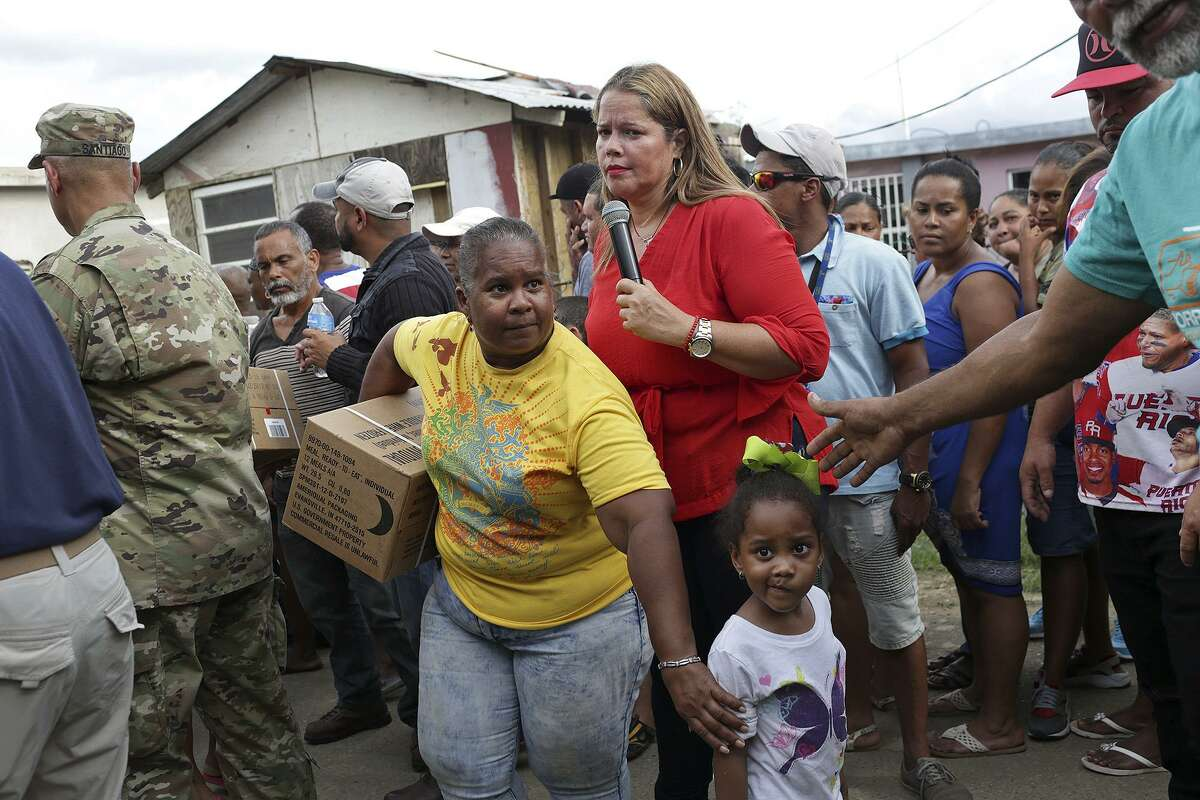 Canovanas Mayor Lornna Soto, center, directs residents of the San Isidro neighborhood as they pick up meals, ready-to-eat, delivered by the U.S. Army National Guard in Canovanas, Puerto Rico, on Thursday, Oct. 5, 2017. The community does not have running water or electricity.