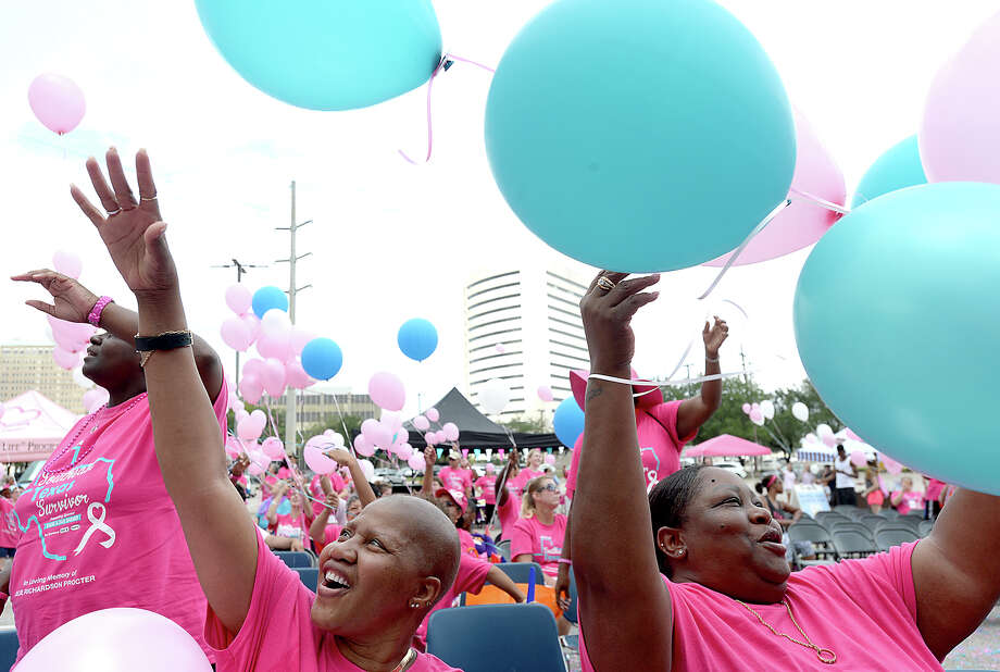 """Nicole Harrison (left), who carried a """"warrior"""" sign as she continues her battle with cancer, and sister Virgia Brown celebrate as they let their balloons go in the final ceremony of the Julie Rogers Gift of Life's """"Walk of Survivorship"""" in downtown Beaumont Saturday.  The event was held in lieu of the annual color run due to Tropical Storm Harvey, but the usual festivities, colorful costuming, and spirit of the event prevailed. This year, survivors included not only those battling or having beaten cancer, but all who have struggled with the impact of Harvey in their own lives and communities throughout Southeast Texas. Photo taken Saturday, October 7, 2017 Kim Brent/The Enterprise Photo: Kim Brent / BEN"""