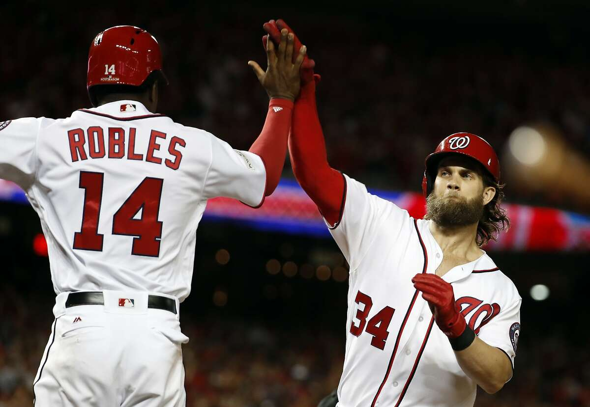 Washington Nationals' Bryce Harper, right, celebrates his two-run homer with Victor Robles (14) in the eighth inning in Game 2 of baseball's National League Division Series against the Chicago Cubs, at Nationals Park, Saturday, Oct. 7, 2017, in Washington. (AP Photo/Alex Brandon)