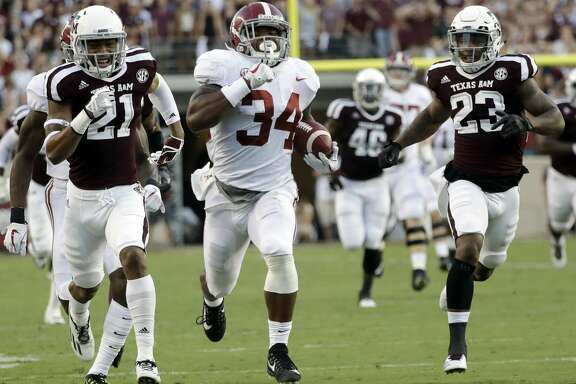 Alabama running back Damien Harris (34) runs for a 75-yard touchdown as Texas A&M's Charles Oliver (21) and Armani Watts (23) pursue during the first quarter of an NCAA college football game Saturday, Oct. 7, 2017, in College Station, Texas. (AP Photo/David J. Phillip)
