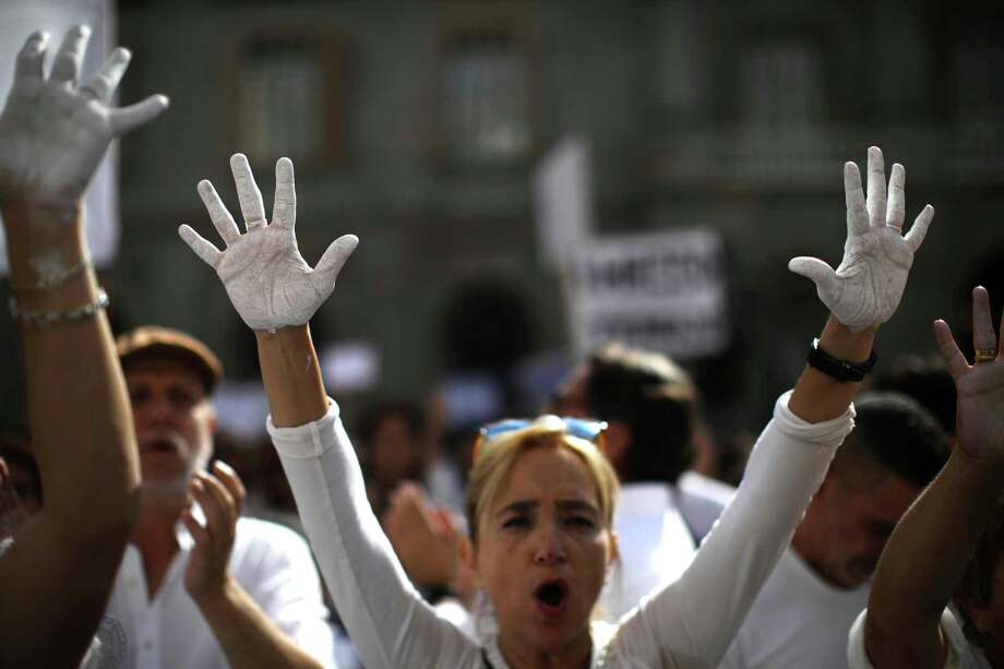 People raise their hands painted in white during a protest in favor of talks and dialogue in Sant Jaume square in Barcelona, Spain, Saturday Oct. 7, 2017. Thousands are gathering at simultaneous rallies in Madrid and Barcelona in a call for dialogue amid a political crisis caused by Catalonia's secession push. (AP Photo/Emilio Morenatti) ORG XMIT: EM101 Photo: Emilio Morenatti / Emilio Morenatti