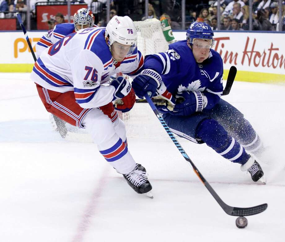 New York Rangers defenseman Brady Skjei (76) and Toronto Maple Leafs centre Leo Komarov (47) vie for control of the puck during second period NHL hockey action in Toronto on Saturday, Oct. 7, 2017. (Cole Burston/The Canadian Press via AP) ORG XMIT: CLB109 Photo: Cole Burston / The Canadian Press