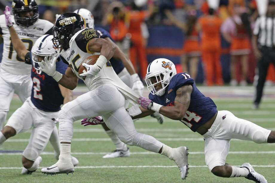 Roadrunner defender C.J. Levine tries to capture Eagle running back Ito Smith as UTSA plays Southern Mississippi at the alamodome on October 7, 2017. Photo: Tom Reel, Staff / San Antonio Express-News / 2017 SAN ANTONIO EXPRESS-NEWS