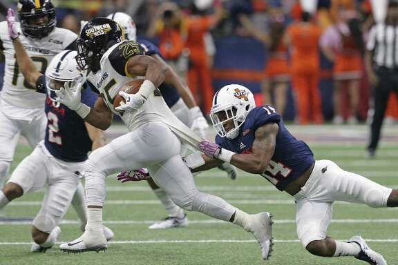 Roadrunner defender C.J. Levine tries to capture Eagle running back Ito Smith as UTSA plays Southern Mississippi at the alamodome on October 7, 2017.