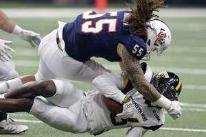 Roadrunner linebacker Josiah Tauaefa slams receiver Quez Watkins to the ground during Saturday's game at the Alamodome.