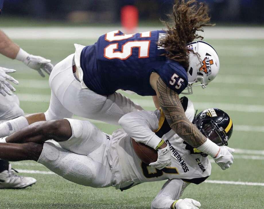 Roadrunner linebacker Josiah Tauaefa slams receiver Quez Watkins to the ground during Saturday's game at the Alamodome. Photo: Tom Reel / San Antonio Express-News / 2017 SAN ANTONIO EXPRESS-NEWS