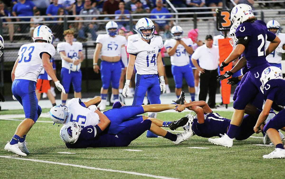 Bronco defender Zach Pike grabs the foot of Barbers Hill quarterback Dalton Holland to help bring him down in the district contest Friday night.