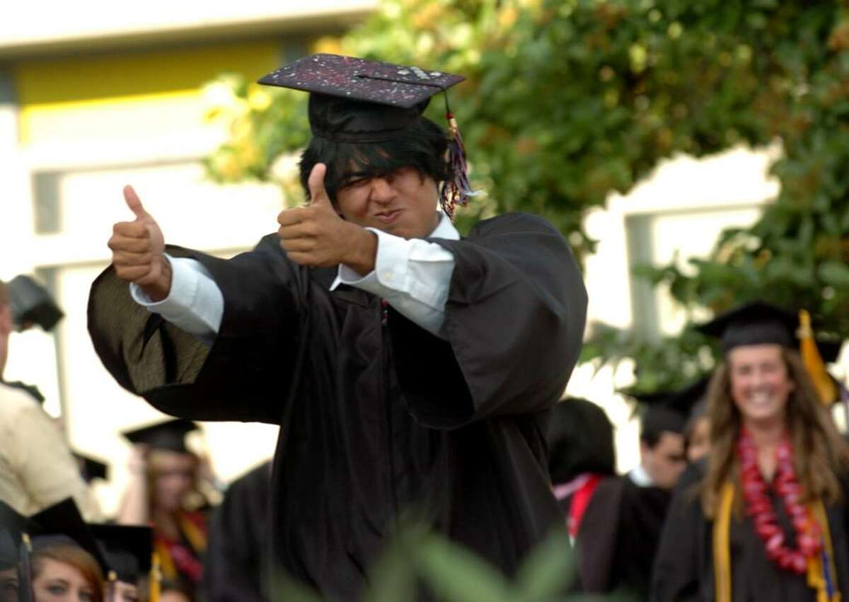 Graduate David Almazan gives the thumbs up sign to Headmaster James Coyne for pronouncing his name correctly, during Fairfield Warde's 6th Annual Commencement Exercises in Fairfield, Conn. on Thursday June 24, 2010.