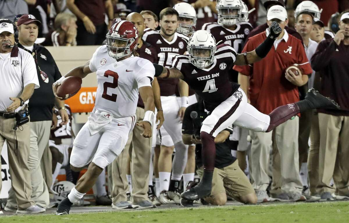 Alabama quarterback Jalen Hurts (2) rushes for a first down as Texas A&M defensive back Derrick Tucker (4) tries to tackle him during the second quarter of an NCAA college football game Saturday, Oct. 7, 2017, in College Station, Texas. (AP Photo/David J. Phillip)