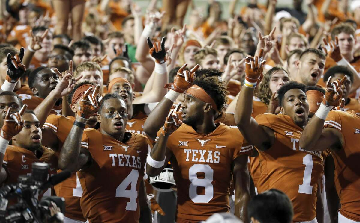 AUSTIN, TX - OCTOBER 07: DeShon Elliott #4 of the Texas Longhorns, Dorian Leonard #8, and John Burt #1 sing the Eyes of Texas after the game against the Kansas State Wildcats at Darrell K Royal-Texas Memorial Stadium on October 7, 2017 in Austin, Texas. (Photo by Tim Warner/Getty Images)
