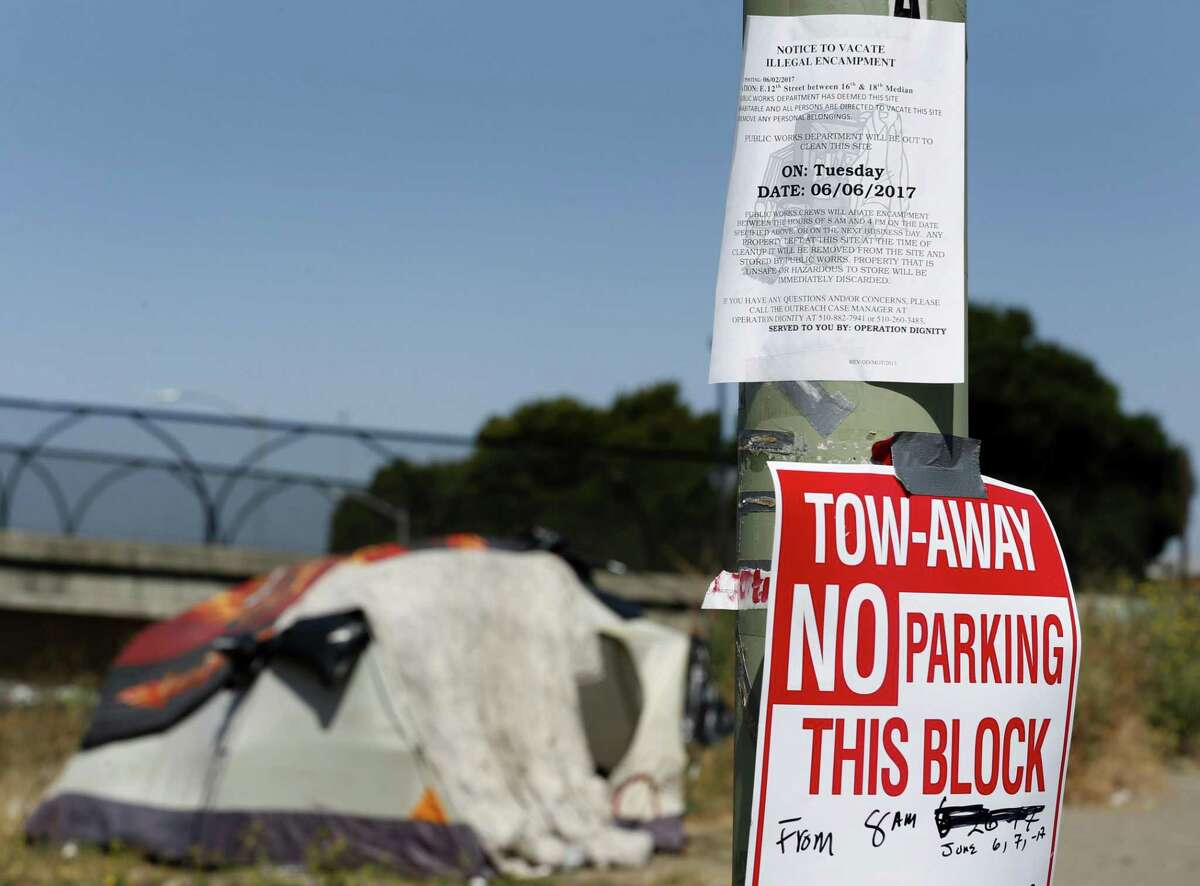 A notice is posted in June warning inhabitants of a homeless encampment to vacate before a public works crew moves in to remove discarded belongings and debris on East 12th Street.