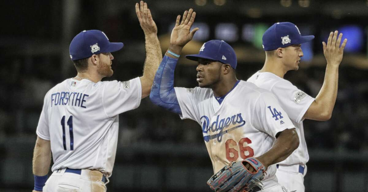 From left, the Los Angeles Dodgers' Logan Forsythe, Yasiel Puig and Corey Seager celebrate an 8-5 win against the Arizona Diamondbacks in Game 2 of the National League Division Series at Dodger Stadium on Saturday, Oct. 7, 2017, in Los Angeles. The Dodgers lead the series, 2-0. (Robert Gauthier/Los Angeles Times/TNS)