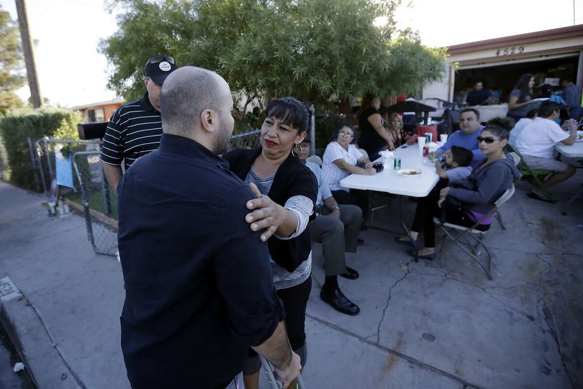 Angelica Silva, the mother of security guard Erick Silva, who was killed in the mass shooting, reaches out to Jeff Bachman, a fellow security guard who was shot in the leg during last Sunday's shooting at a music festival, as he arrives to the Silva house, Friday, Oct. 6, 2017, in Las Vegas. Silva was among the dozens of people killed in the attack. Bachman and another guard were injured. Despite the fresh trauma and losing one of their own, many of the company's guards are returning to work events for the first time again this weekend. (AP Photo/Gregory Bull)