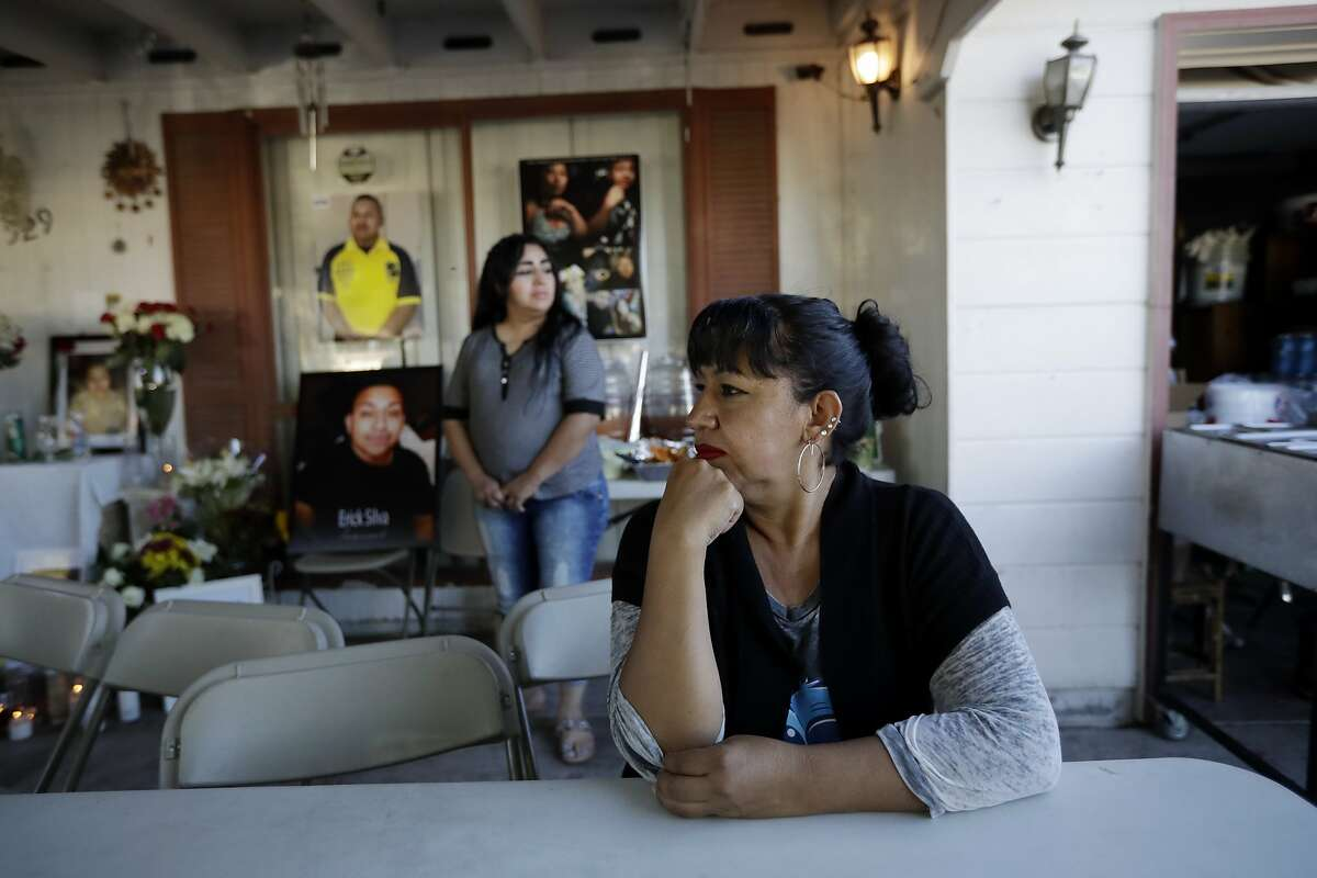 Angelica Silva, the mother of mass shooting victim and security guard Erick Silva sits in front of a candle-lit memorial with photos of Erick and flowers to honor her son during a meal for friends and family at their home Friday, Oct. 6, 2017, in Las Vegas. Silva was among the dozens of people killed in the attack. Despite the fresh trauma and losing one of their own, many of the security company's guards are returning to work events for the first time again this weekend. (AP Photo/Gregory Bull)