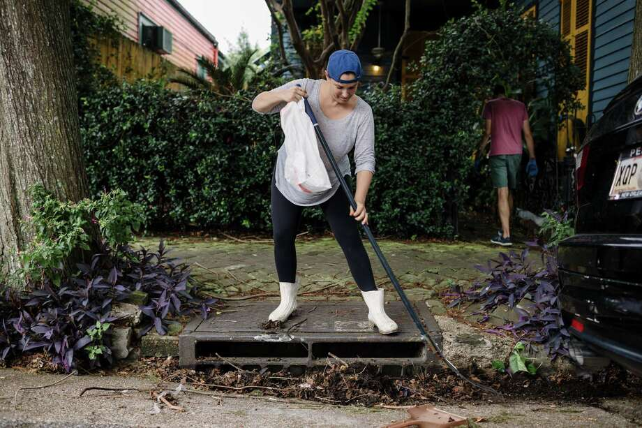 A woman clears the storm drain in front of her home in New Orleans last year. Photo: BRYAN TARNOWSKI/AFP/Getty Images