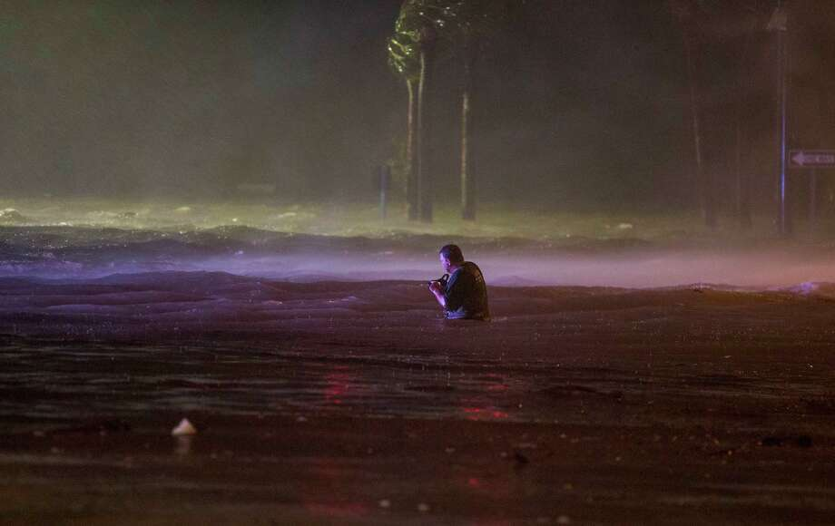 BILOXI,MS-OCTOBER 8, 2017:  Lanny Dean, from Tulsa, Oklahoma, takes video as he wades along a flooded Beach Boulevard next to Harrahs Casino as the eye of Hurricane Nate pushes ashore in Biloxi, Mississippi October 8, 2017.  Hurricane Nate flooded the parking garage and first floors of Golden Nugget, Harrahs and other casinos as it made a second landfall on the Mississippi coast as a category 1 storm. (Photo by Mark Wallheiser/Getty Images) Photo: Mark Wallheiser/Getty Images