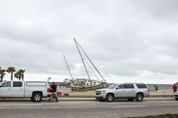 BILOXI, MS - OCTOBER 8:  Television film crews gather around a large sailboat that was washed ashore on a Biloxi beach by Hurricane Nate on October 8, 2017 in Biloxi, Mississippi.  Hurricane Nate made it's second landfall along the north Mississippi Gulf Coast as a category 1 hurricane Sunday before weakening to a tropical storm.  (Photo by Mark Wallheiser/Getty Images)