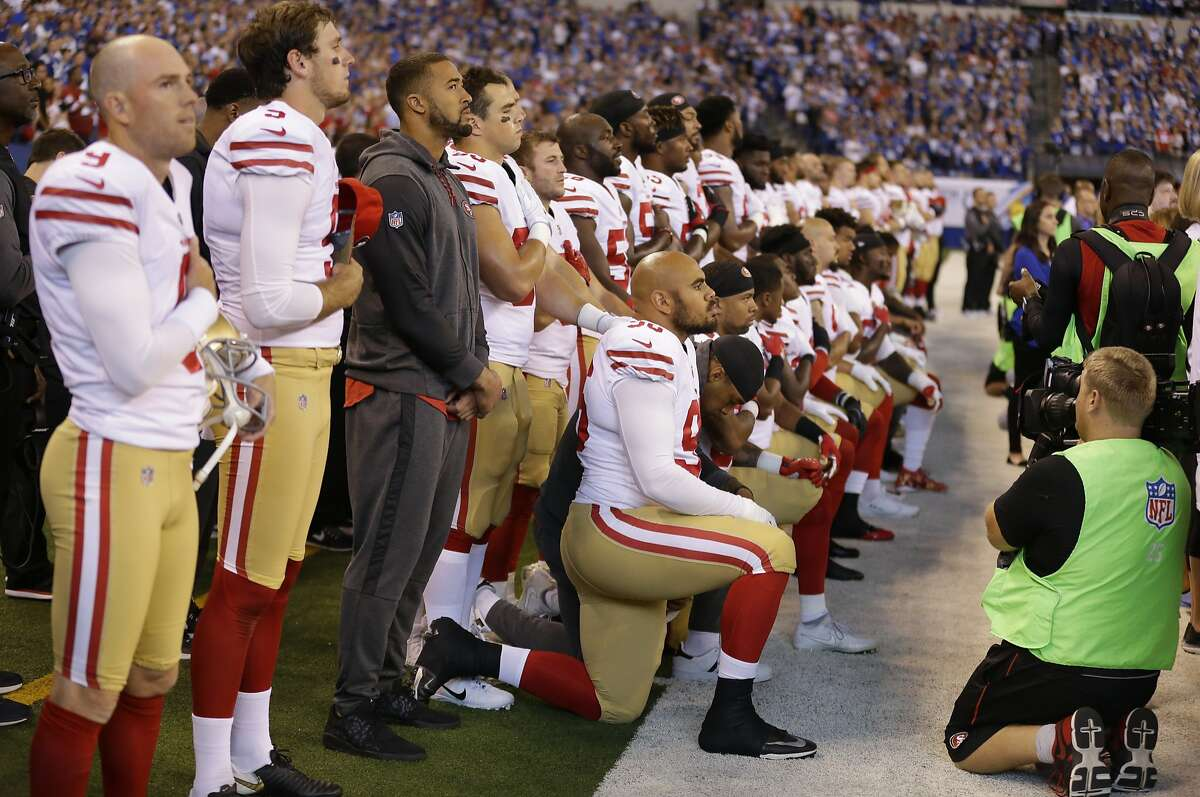 Member of the San Francisco 49ers kneel during the playing of the national anthem before an NFL football game against the Indianapolis Colts, Sunday, Oct. 8, 2017, in Indianapolis. (AP Photo/Michael Conroy)