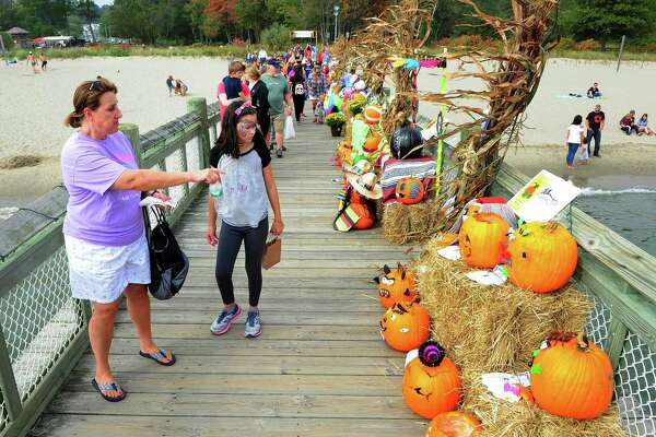 Lisa Curtin, of Milford, and her niece Caitlin, 9, check out one of the displays during the Pumpkins on the Pier Festival at Walnut Beach in Milford, Conn., on Saturday Oct. 7, 2017. The festival included a pumpkin patch with over 3000 pumpkins, games and rides for the kids, pumpkin carving and decorating, food trucks, craft vendors, and of course the beautifully decorated pier.