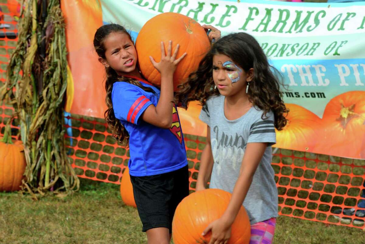 Alani Velez, 10, of Milford, and her sister Lexi, in front, carry pumpkins at the Boys and Girls Club pumpkin patch during the Pumpkins on the Pier Festival at Walnut Beach in Milford, Conn., on Saturday Oct. 7, 2017. The festival included a pumpkin patch with over 3000 pumpkins, games and rides for the kids, pumpkin carving and decorating, food trucks, craft vendors, and of course the beautifully decorated pier.