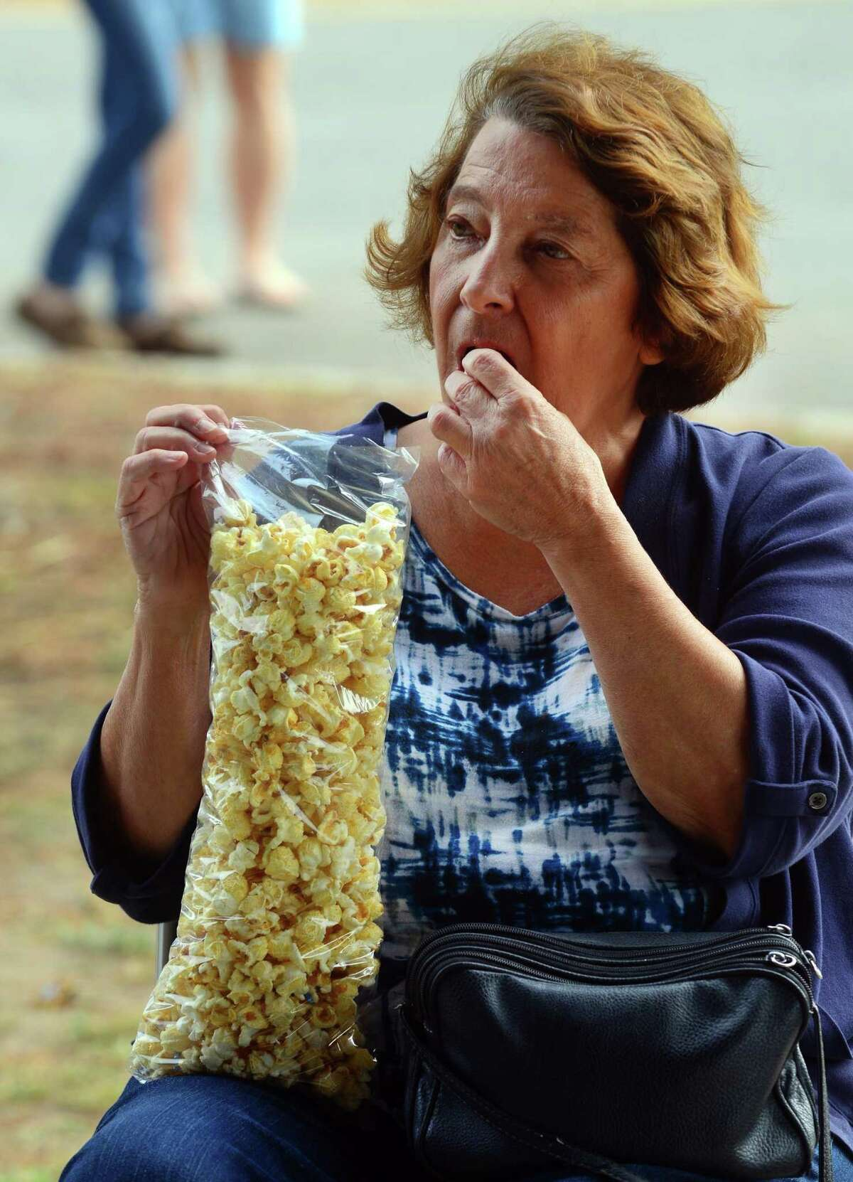 Carol Tiernan, of Milford, enjoys a bag of kettle corn during the Pumpkins on the Pier Festival at Walnut Beach in Milford, Conn., on Saturday Oct. 7, 2017. The festival included a pumpkin patch with over 3000 pumpkins, games and rides for the kids, pumpkin carving and decorating, food trucks, craft vendors, and of course the beautifully decorated pier.