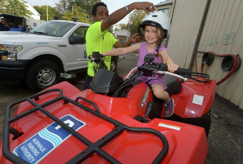 Norwalk Parking Authority employee Simon Zerufael helps Isla Depmsey, 5, of Wilton, at top, gets fitted with a helment while sitting on a quad during the Norwalk Fire, Police, and Public Works Departments and Norwalk EMS Open House and Touch- a- Truck Sept. 30 at the Public Works Center and fire training tower on South Smith Street in Norwalk. All four Departments featured hands-on activities, give-aways and demonstrations for all ages. Photo: Erik Trautmann / Hearst Connecticut Media / Norwalk Hour