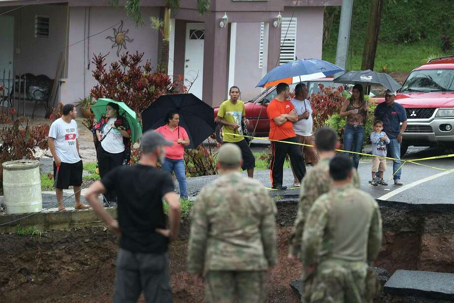BARRANQUITAS, PUERTO RICO - OCTOBER 07: People look on as U.S. Army 1st Special Force Command soldiers check for people in need as heavy rains fall on the area days after Hurricane Maria swept through the island on October 7, 2017 in Barranquitas, Puerto Rico. The team of soldiers are delivering supplies to people as well as checking on the well being of people caught up in the natural disaster.  (Photo by Joe Raedle/Getty Images) Photo: Joe Raedle / Getty Images / 2017 Getty Images