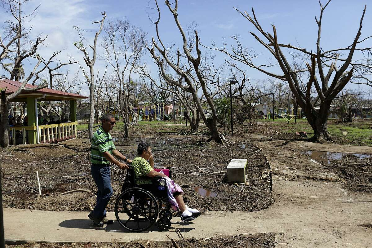 Luis Alberto Santos pushes his wife, Minerva Ayala, through a park after see the team of medical professionals volunteering in Esperanza on the island of Vieques, Puerto Rico on Friday, Oct. 6, 2017. Ayala has lung cancer and recently had bone metatasis surgery. She is undergoing chemotherapy on the mainland but has not been able to see her oncologist and has no way of communicating with doctors. Their son lives in Ocala, FL and wants her to get treatment there.