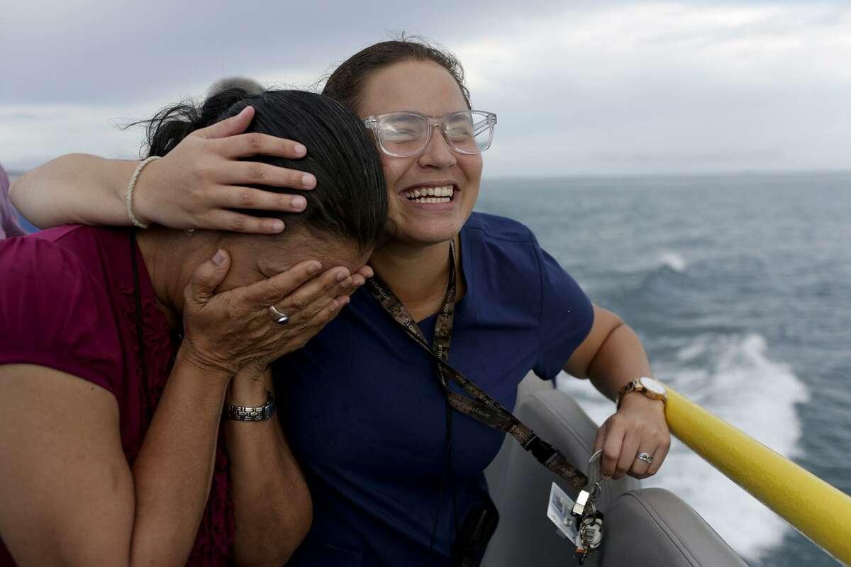Shaykarie Tirado, 21, comforts Miriam Sobá Peterson as they near the island of Vieques, Puerto Rico.