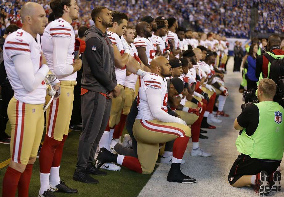 More than 20 members of the 49ers kneel while teammates stand during the playing of the national anthem Sunday. Vice President Mike Pence left the game shortly thereafter. Photo: Michael Conroy, Associated Press
