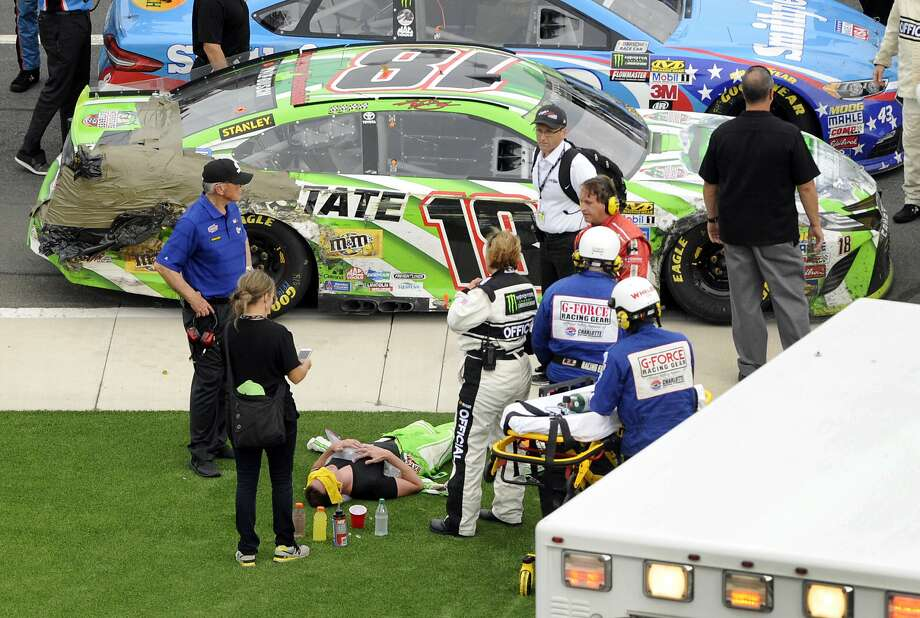 Emergency personnel assist driver Kyle Busch next to his damaged car after a NASCAR Cup Series auto race at Charlotte Motor Speedway in Concord, N.C., Sunday, Oct. 8, 2017. (AP Photo/Mike McCarn) Photo: Mike McCarn, Associated Press