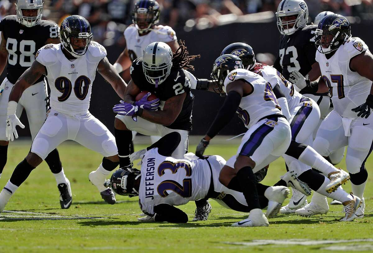 Marshawn Lynch (24) drives for a few more yards in the first quarter as the Oakland Raiders played the Baltimore Ravens at the Oakland Coliseum in Oakland, Calif., on Sunday, October 8, 2017.