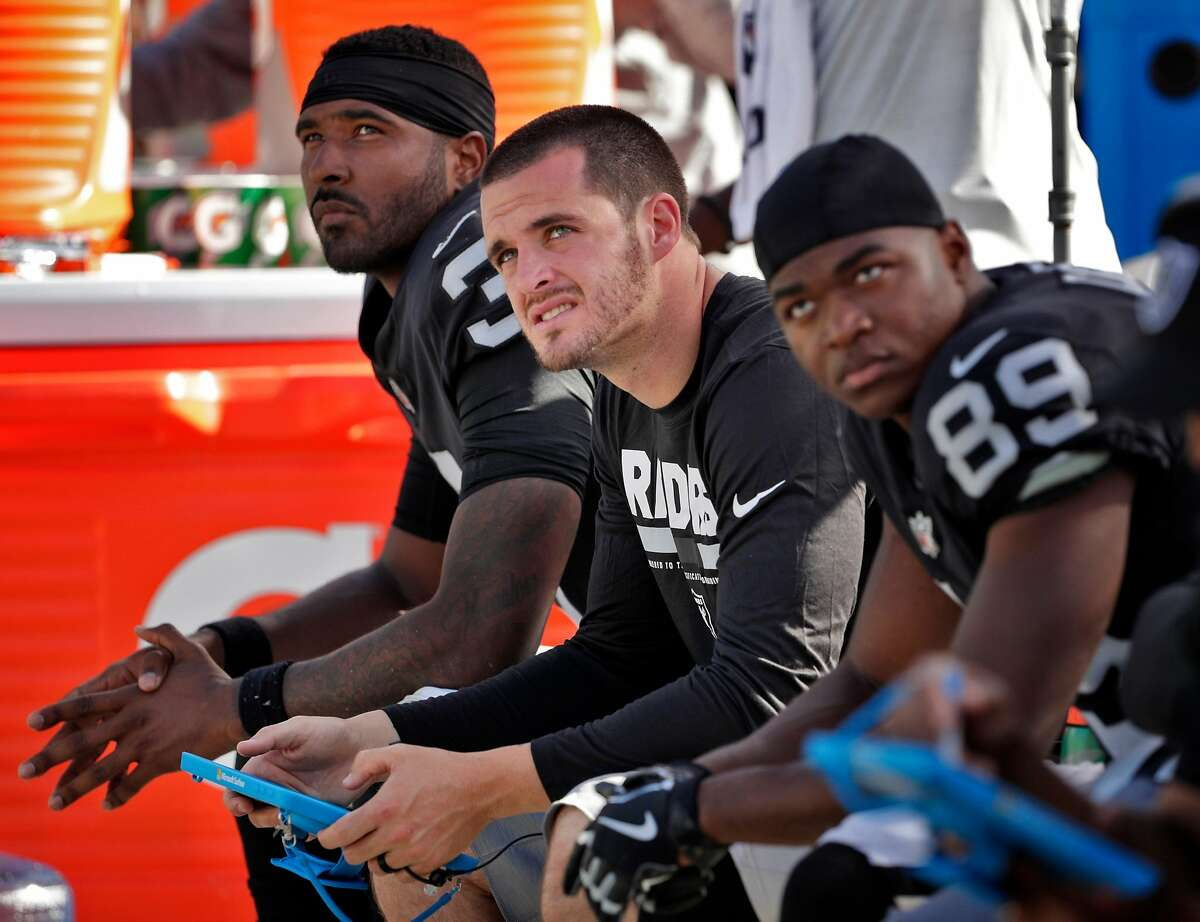EJ Manuel (3), Derek Carr (4) and Amari Cooper (89) on the bench as the Ravens drive down the field in the second half as the Oakland Raiders played the Baltimore Ravens at the Oakland Coliseum in Oakland, Calif., on Sunday, October 8, 2017.