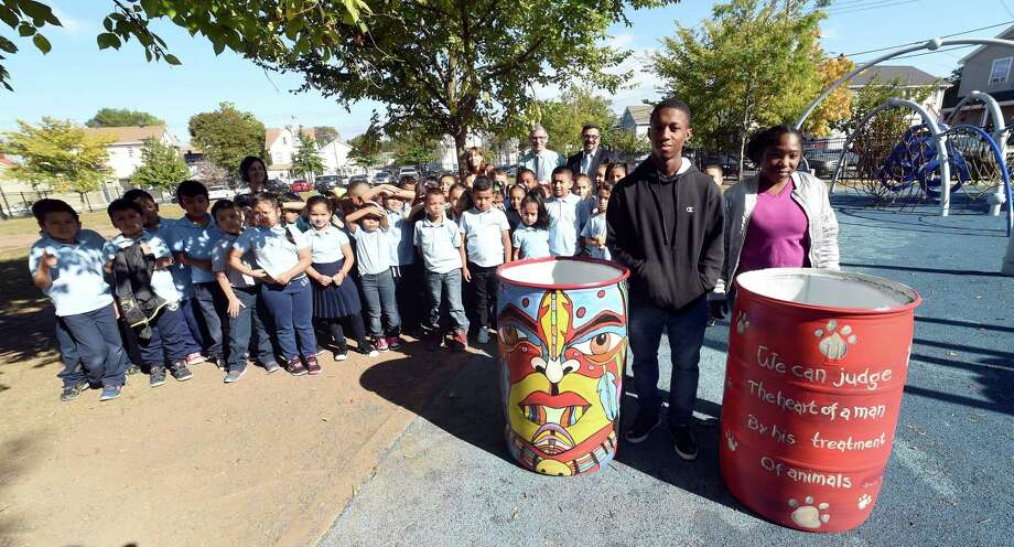Elijah Joyner, right, 18, and Roniesh Murdock, far right, 19 of New Light High School in New Haven are photographed on Oct. 6, with two waste barrels they helped create for the Christopher Columbus Family Academy playground. In the background are second graders from the academy. Photo: Arnold Gold / Hearst Connecticut Media / New Haven Register