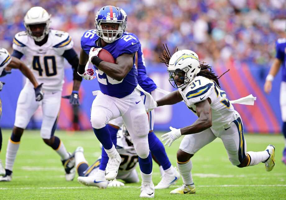 EAST RUTHERFORD, NJ - OCTOBER 08:  Orleans Darkwa #26 of the New York Giants runs the ball past Jahleel Addae #37 of the Los Angeles Chargers for a first quarter touchdown during an NFL game at MetLife Stadium on October 8, 2017 in East Rutherford, New Jersey.  (Photo by Steven Ryan/Getty Images) ORG XMIT: 700070665 Photo: Steven Ryan / 2017 Getty Images
